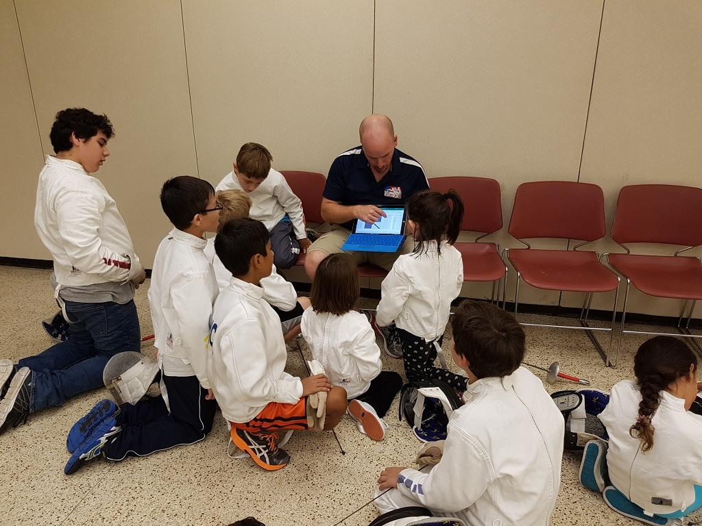 We were so caught up in the bouts we showed the kids that we forgot to take any pictures of the group watching the Olympic fencing. It basically looked like this picture, where Dan is showing the kids the pool sheet from their end-of-camp tournament.