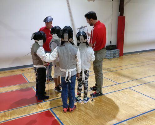 Coach Benoit talks to Y10 fencers