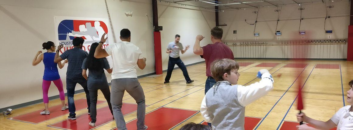 A group of adult fencers practices footwork