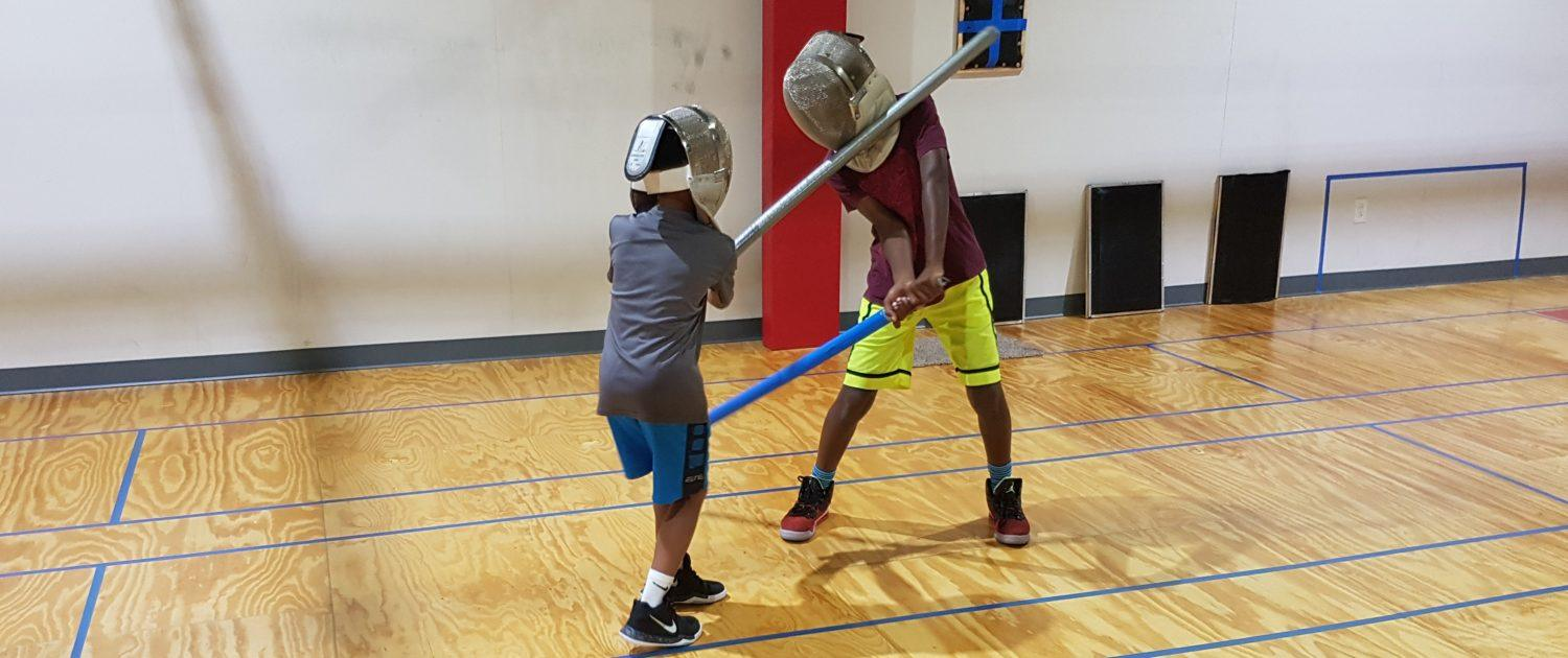 Two kids learn light saber combat