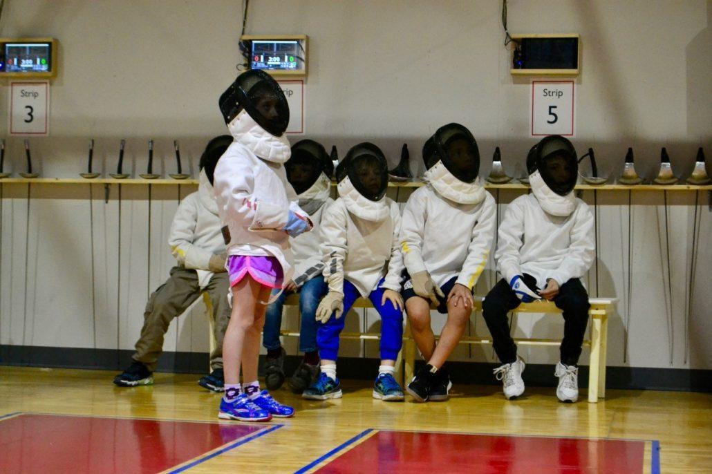 A group of young fencers waits for a turn to fence